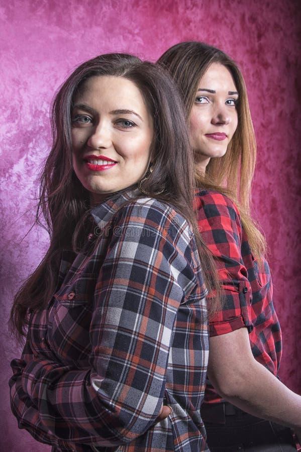 Dos mujeres hermosas jovenes en camisas de tela escocesa se colocan con sus partes posteriores el uno al otro imagenes de archivo