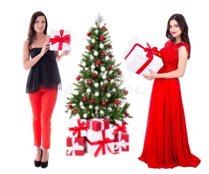 Dos mujeres hermosas jovenes en rojo con las cajas de regalo y el decorat grandes imagen de archivo libre de regalías