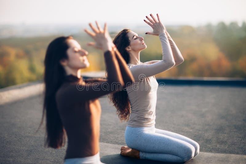 Dos mujeres hermosas jovenes que hacen asana de la yoga en el tejado al aire libre imagenes de archivo