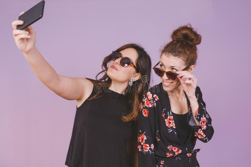Dos mujeres hermosas jovenes que se divierten que toma un selfie con el móvil imágenes de archivo libres de regalías