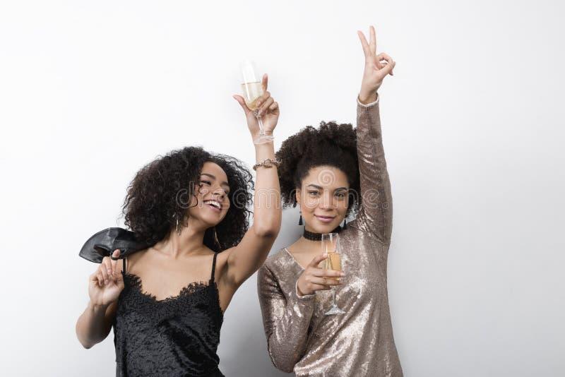 Dos mujeres hermosas que bailan y que beben el champán imagen de archivo libre de regalías