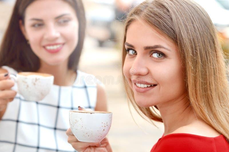 Dos mujeres hermosas que beben el café en la barra exterior fotografía de archivo libre de regalías