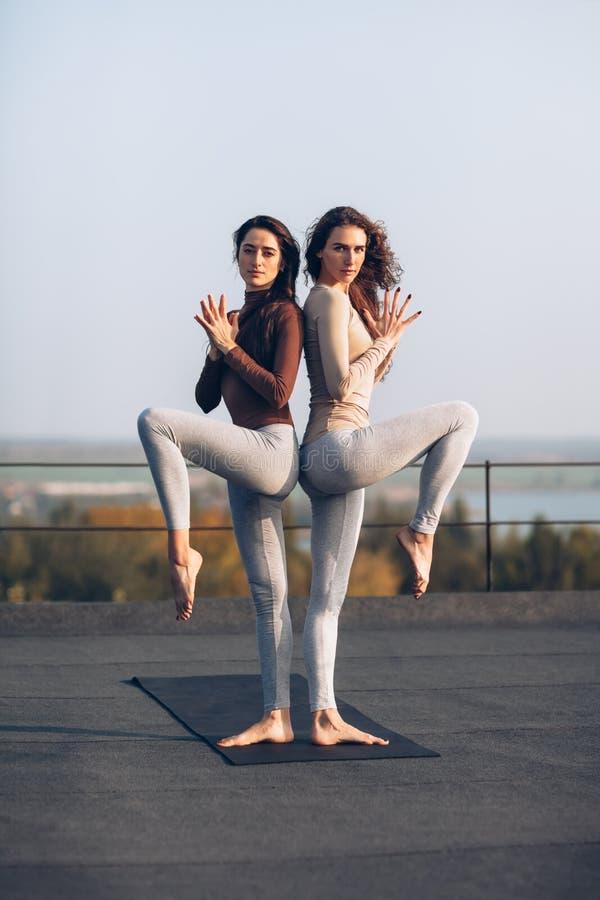 Dos mujeres hermosas que hacen asana de la yoga en el tejado al aire libre fotografía de archivo
