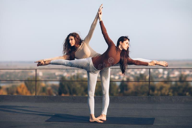 Dos mujeres hermosas que hacen virabhadrasana del asana de la yoga en el tejado foto de archivo