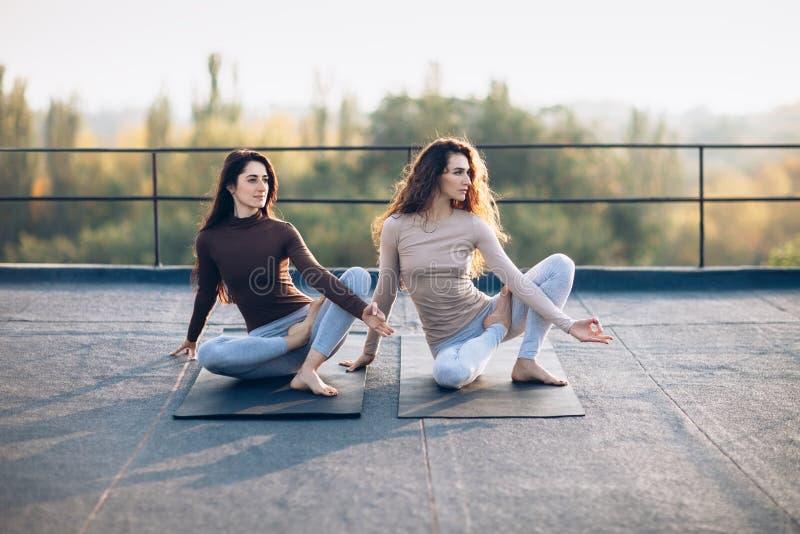 Dos mujeres hermosas que hacen virabhadrasana del asana de la yoga en el tejado foto de archivo libre de regalías