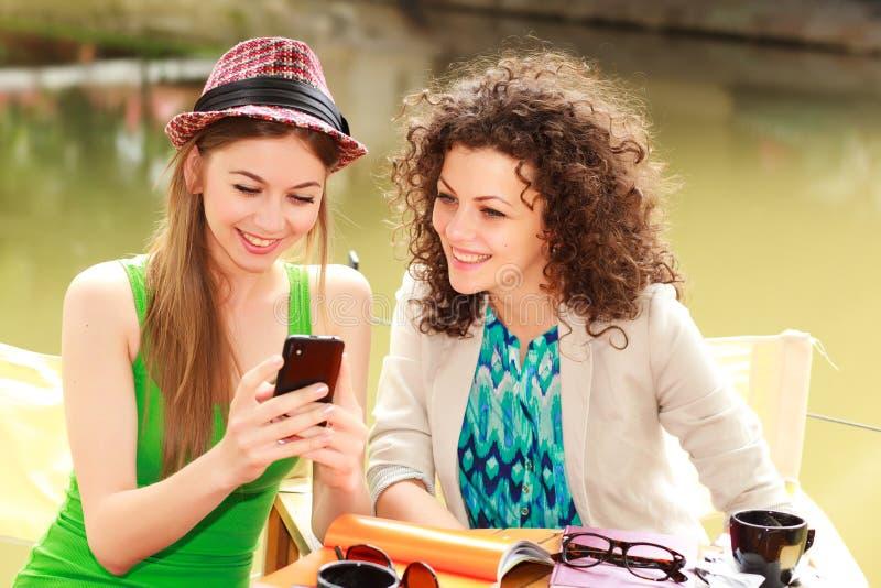 Dos mujeres hermosas que juegan en un elegante-teléfono foto de archivo