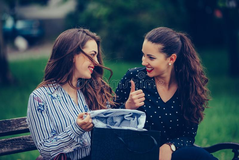 Dos mujeres hermosas que se sientan en el banco de parque despu?s de hacer compras y de compartir sus nuevas compras con uno a imagen de archivo