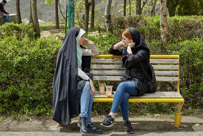 Dos mujeres iraníes están hablando en el banco, Teherán foto de archivo libre de regalías