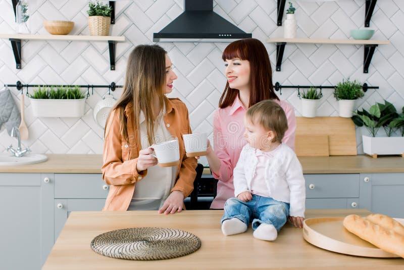 Dos mujeres jovenes alegres que se sientan en una tabla con las tazas en una cocina Poco bebé se está sentando en la tabla Desayu imagenes de archivo