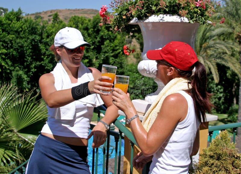 Dos mujeres jovenes, atractivas, aptas y sanas que beben el jugo después de un juego caliente del tenis imagen de archivo