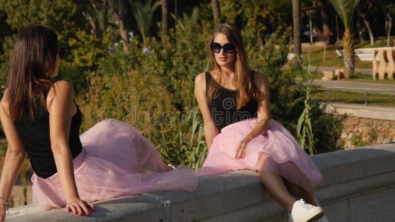 Dos mujeres jovenes atractivas en las faldas y las zapatillas de deporte de Tulle que se sientan por el mar fotos de archivo libres de regalías