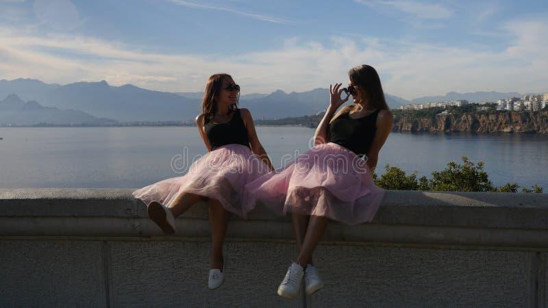 Dos mujeres jovenes atractivas en las faldas y las zapatillas de deporte de Tulle que se sientan por el mar fotografía de archivo libre de regalías