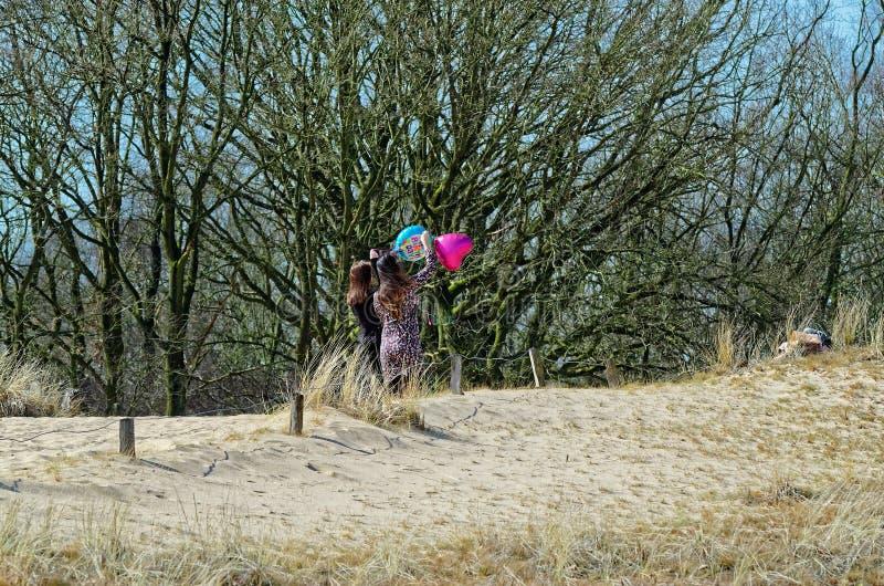Dos mujeres jovenes con impulsos del helio en una duna arenosa fotos de archivo libres de regalías