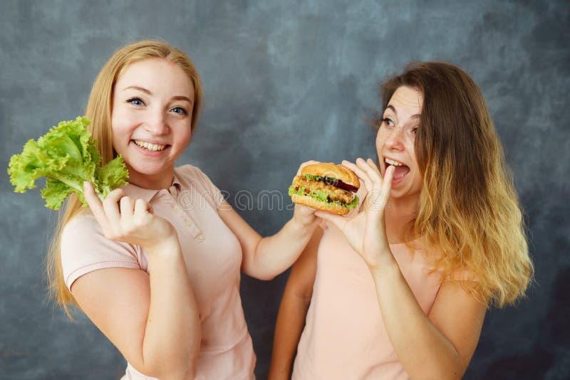 Dos mujeres jovenes con la ensalada y la hamburguesa fotos de archivo libres de regalías