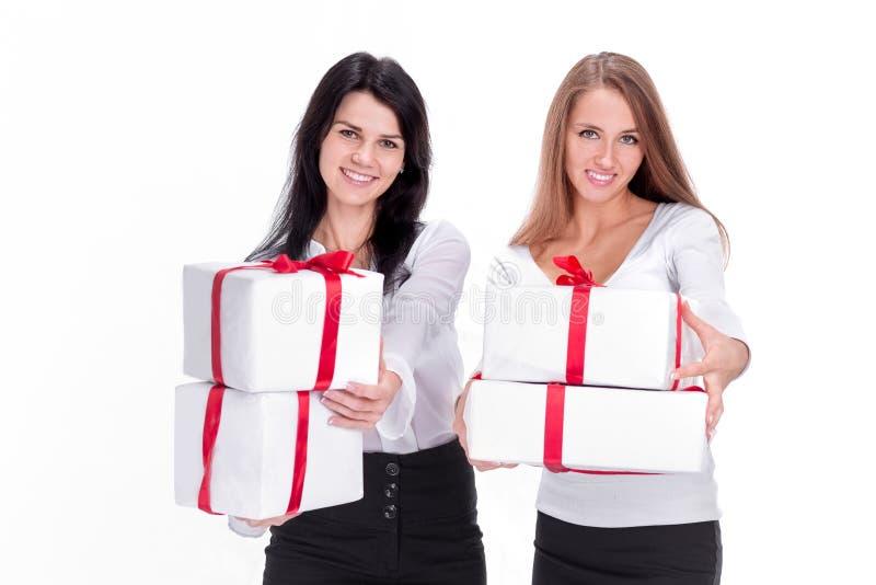 Dos mujeres jovenes con las cajas de regalo Aislado en blanco fotos de archivo libres de regalías