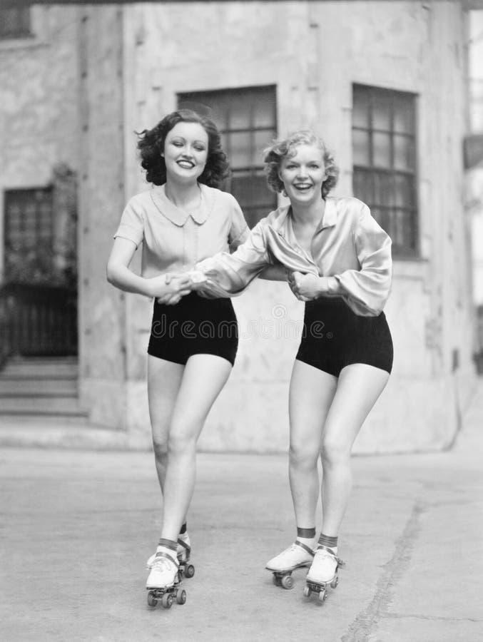 Dos mujeres jovenes con las cuchillas del rodillo que patinan en el camino y la sonrisa (todas las personas representadas no son  foto de archivo
