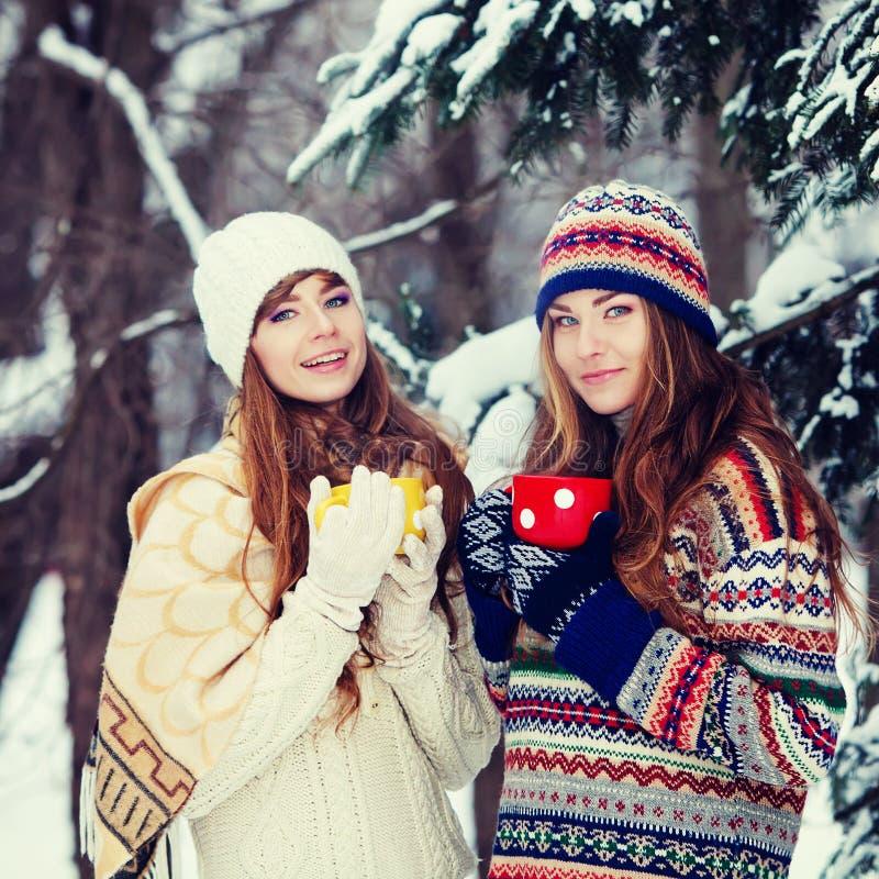 Dos mujeres jovenes con las tazas coloridas que beben el té al aire libre y el smil imagen de archivo libre de regalías
