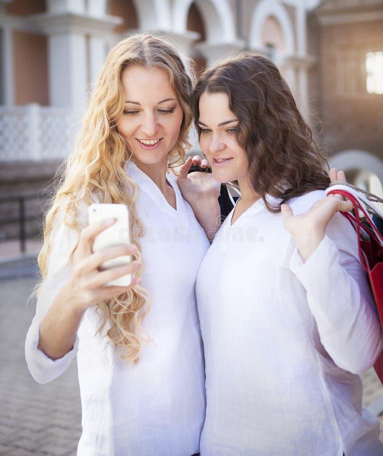 Dos mujeres jovenes con los panieres que toman un selfie fotos de archivo