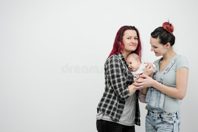 Dos mujeres jovenes con un bebé en un fondo blanco Matrimonio homosexual y adopción, par lesbiano homosexual fotografía de archivo libre de regalías