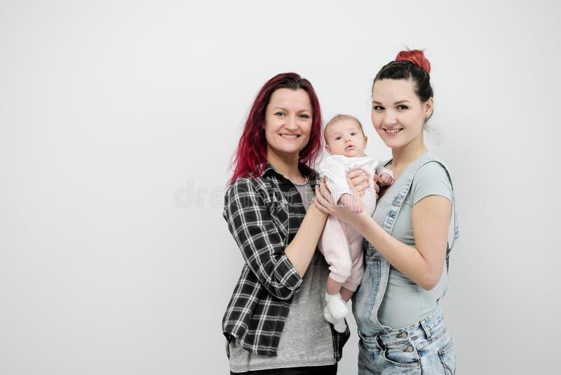 Dos mujeres jovenes con un bebé en un fondo blanco Matrimonio homosexual y adopción, par lesbiano homosexual imagen de archivo