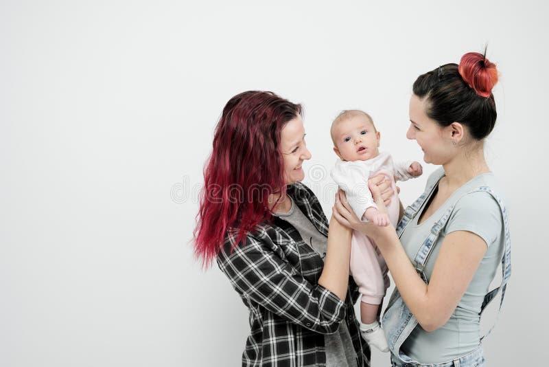 Dos mujeres jovenes con un bebé en un fondo blanco Matrimonio homosexual y adopción, par lesbiano homosexual foto de archivo