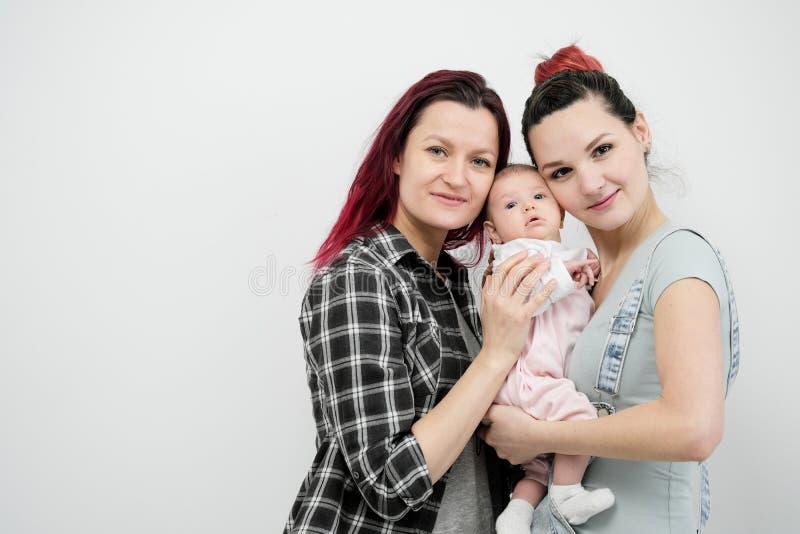 Dos mujeres jovenes con un bebé en un fondo blanco Matrimonio homosexual y adopción, par lesbiano homosexual fotos de archivo