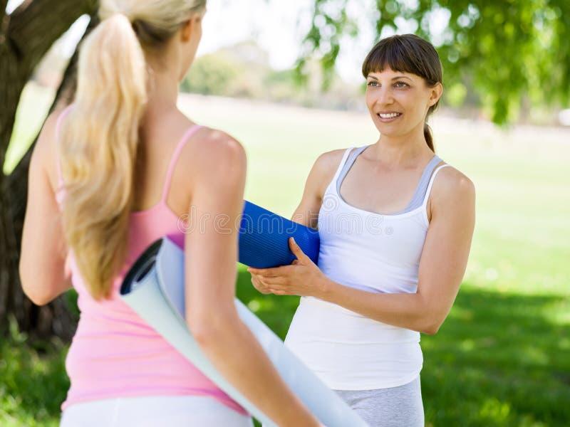 Dos mujeres jovenes con una estera del gimnasio que charlan en el parque fotos de archivo