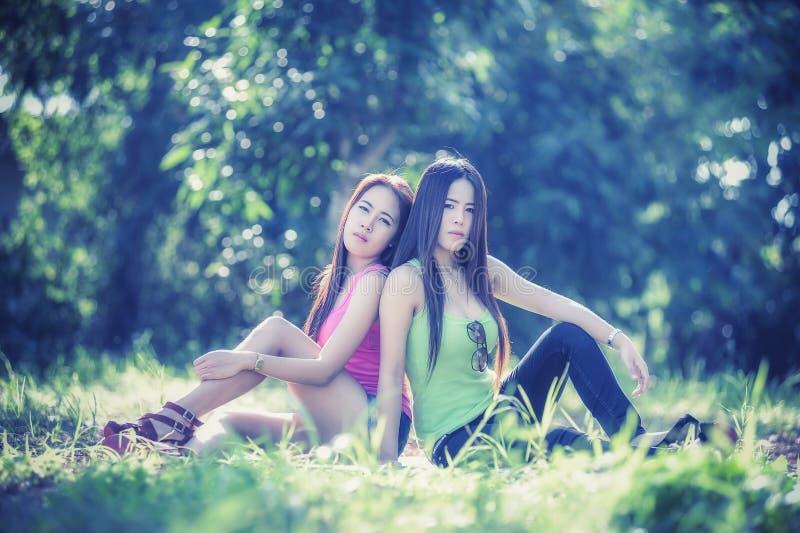 Download Dos Mujeres Jovenes De Asia Que Se Sientan En Hierba Foto de archivo - Imagen de goce, travieso: 64201624