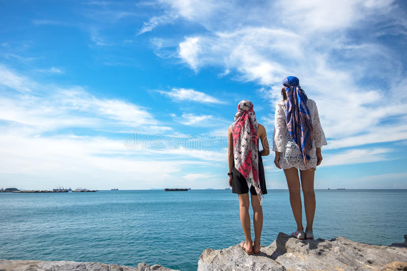 Dos mujeres jovenes del viajero que ven la playa hermosa y el cielo azul imágenes de archivo libres de regalías