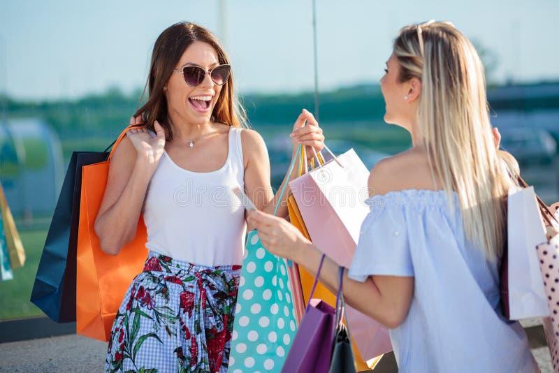 Dos mujeres jovenes delante de la ventana de la tienda, bolsos de compras que llevan imagen de archivo libre de regalías