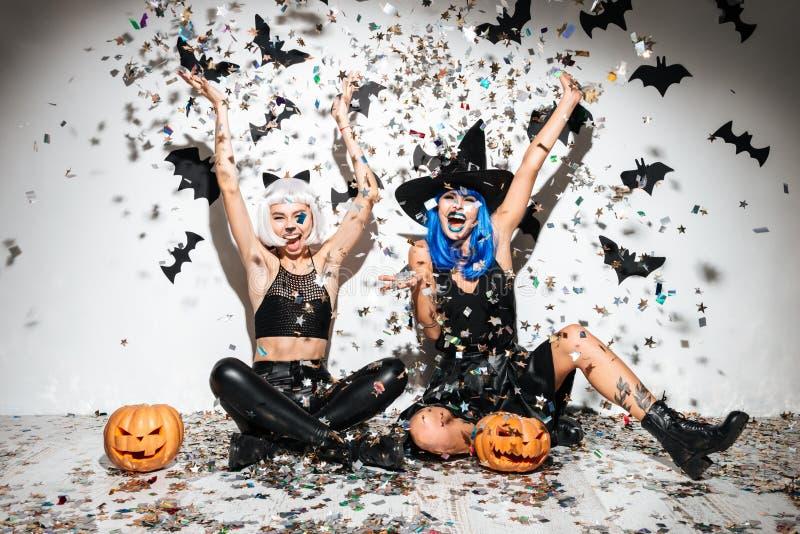 Dos mujeres jovenes divertidas en la presentación de cuero de los disfraces de Halloween imagen de archivo