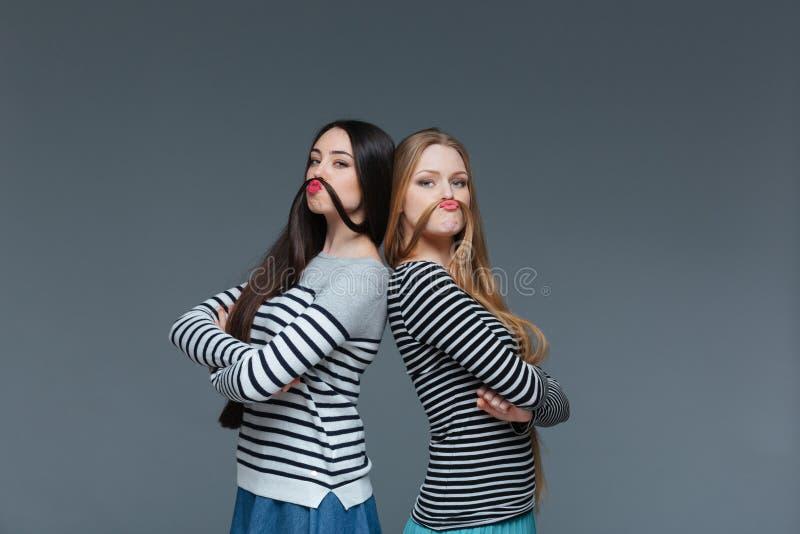 Dos mujeres jovenes divertidas que hacen el bigote con su pelo imagenes de archivo