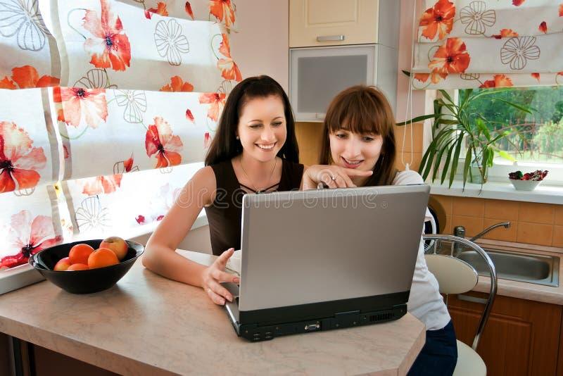Dos mujeres jovenes en la cocina con una computadora portátil imagen de archivo