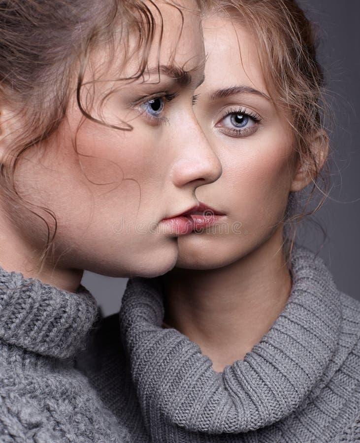 Dos mujeres jovenes en suéteres grises en fondo gris g hermoso imagenes de archivo