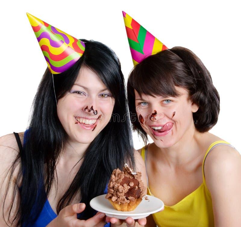 Dos mujeres jovenes felices con la torta fotografía de archivo