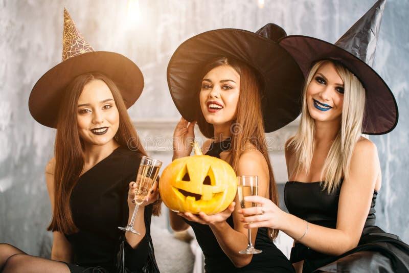 Dos mujeres jovenes felices en disfraces de Halloween negros de la bruja en partido fotos de archivo