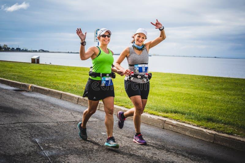 Dos mujeres jovenes felices en el primer kilómetro del maratón imágenes de archivo libres de regalías