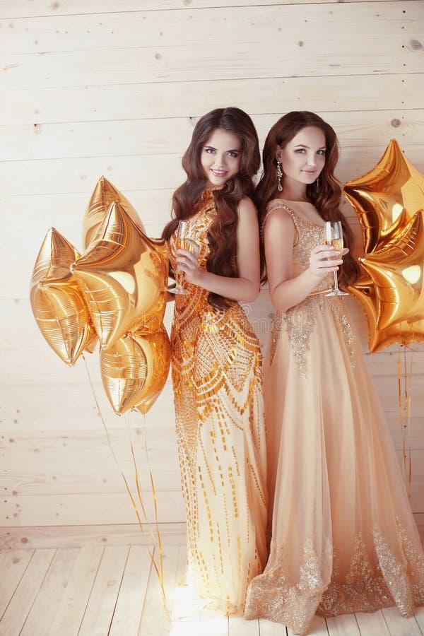 Dos mujeres jovenes felices en partido con los vidrios de champán Cheerf fotografía de archivo