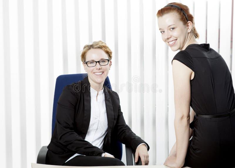 Dos mujeres jovenes felices en una oficina foto de archivo