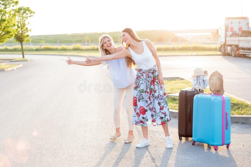 Dos mujeres jovenes felices que tienen un gran rato mientras que hace autostop fotos de archivo libres de regalías