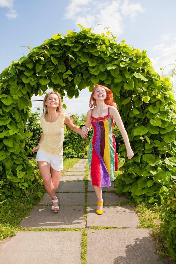 Dos mujeres jovenes felices runing en un parque imágenes de archivo libres de regalías