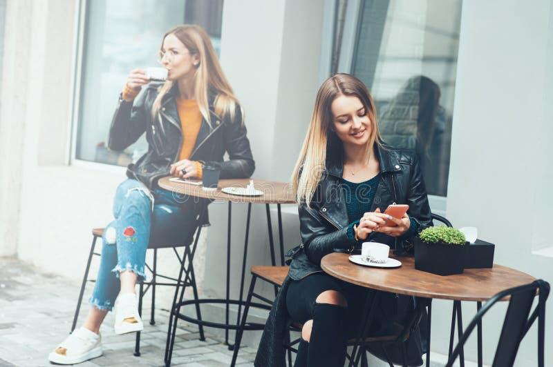 Dos mujeres jovenes hermosas en de moda llevan sentarse al aire libre en café y usar smartphones mientras que beben el café Messa imagen de archivo