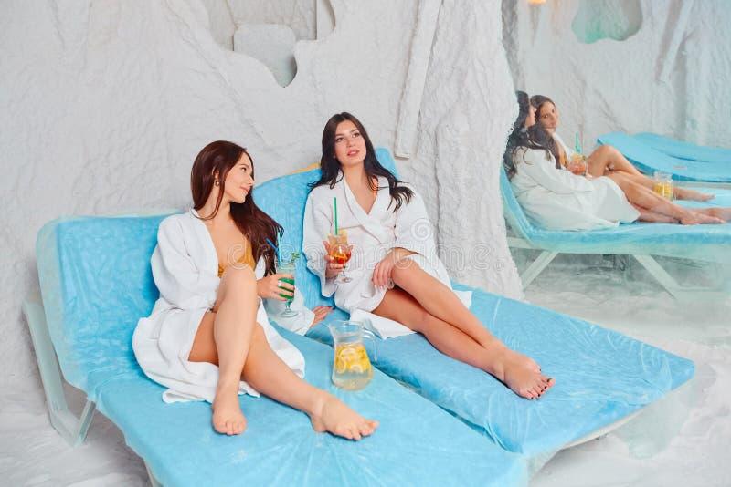 Dos mujeres jovenes hermosas en las capas blancas se relajan en el cuarto de la sal del balneario fotos de archivo libres de regalías