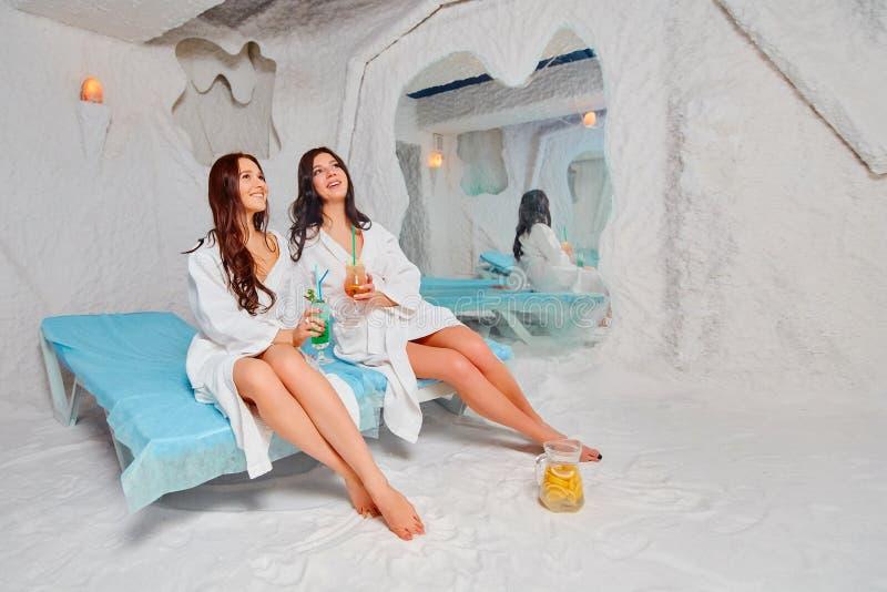 Dos mujeres jovenes hermosas en las capas blancas se relajan en el cuarto de la sal del balneario fotos de archivo