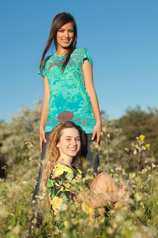 Dos mujeres jovenes hermosas en prado floreciente imagen de archivo