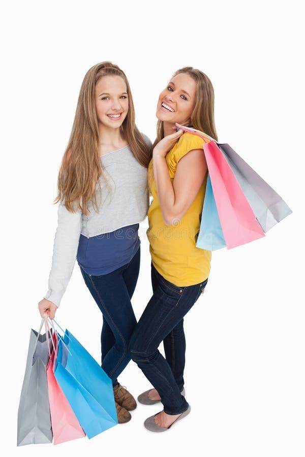 Dos mujeres jovenes hermosas que sostienen bolsos de compras fotos de archivo