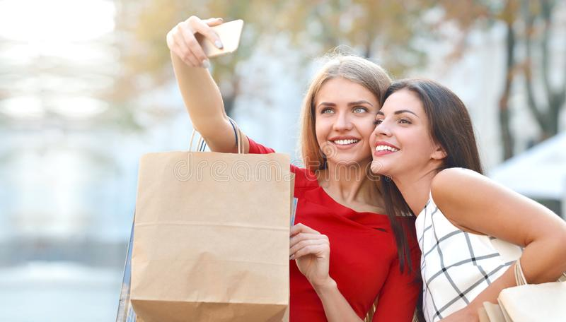 Dos mujeres jovenes hermosas que toman un selfie con su teléfono celular foto de archivo