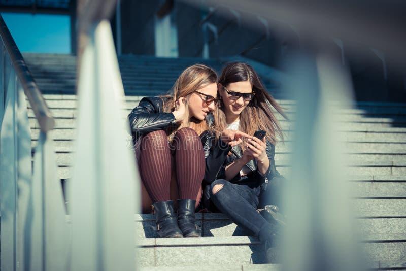 Dos mujeres jovenes hermosas que usan el teléfono elegante imagen de archivo