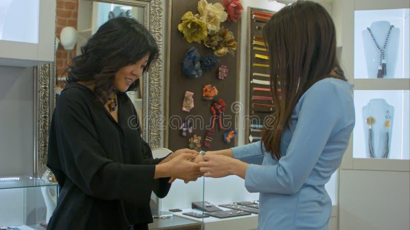 Dos mujeres jovenes intentan encendido una joyería desined en una tienda imagen de archivo libre de regalías