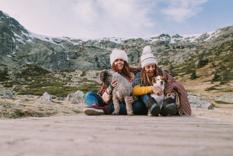 Dos mujeres jovenes juegan con sus perros en el medio del prado imagenes de archivo